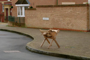 Wooden manger at a pavement edge.